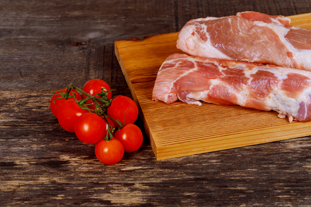 Pork steak on the wooden background with cherry tomatoes Stock Photo