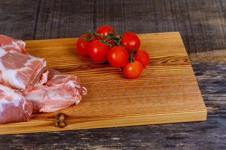 fresh pork with ingredients for cooking on wooden board Pork meat tomatoes a wooden board Stock Photo