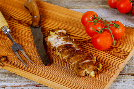 Slow cooked pulled meat pork on chopping board with mixed tomato, wood background, view from above, close-up Stok Fotoğraf