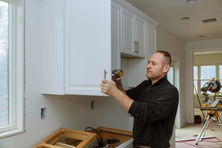 The worker sets a new handle on the white cabinet with a screwdriver installing kitchen cabinets Stok Fotoğraf