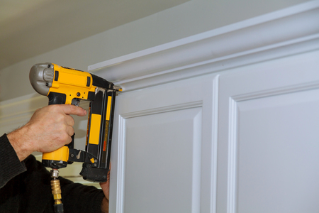 Wood working using brad nail air gun to Crown Moulding on white kitchen cabinets framing trim, with the all power tools Stock Photo