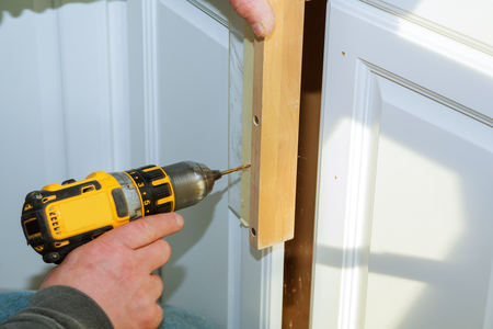 Worker use drill to repair furniture and drills the cabinet door a cordless screwdriver, close up. Stock Photo