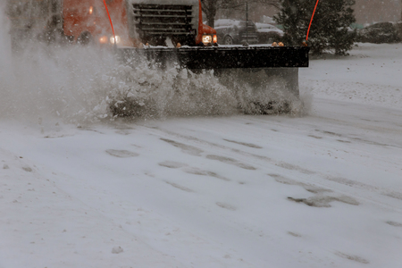 Cleaning road from snow storm. Snow remover truck cleaning city streets in snow storm Stock Photo