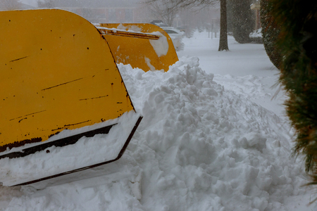 Excavator cleans the streets of large amounts of snow in city. Winter time concept. Standard-Bild