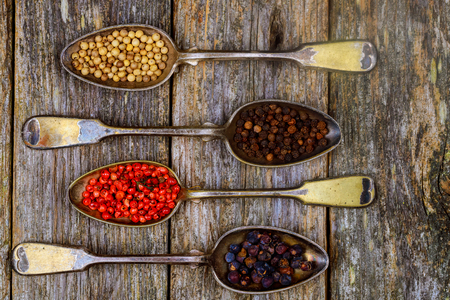 Different types of pepper spice in vintage spoons on wood background different types of spice peppers