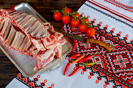 Lamb mutton with spices, red pepper and garlic bulbs on slate and wooden table. Top view. Stock Photo