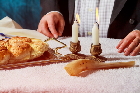 Challah or Hala is a traditional jewish sweet fresh sabbath bread loaf. Hands of men keep bread and two wax candles in candlesticks.