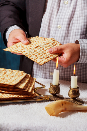 passover matzah is a traditional jewish fresh sabbath bread loaf. Hands of men keep bread and two wax candles in candlesticks. Imagens