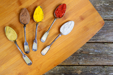 Various colorful spices in old vintage spoons. Top view with copy space Different spice