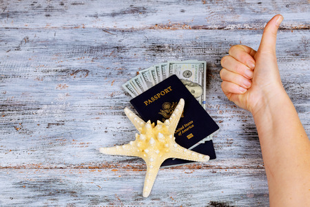 preparation for vacation, a passport with money to rest on the table and sea star travel money