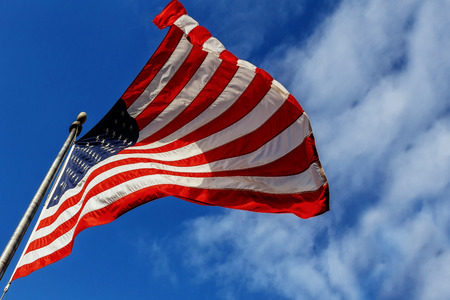 American flag flying, flag USA over blue sky background 스톡 콘텐츠