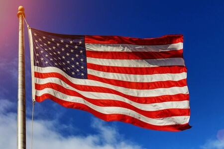 American flag - star and stripes floating over a cloudy blue sky Banco de Imagens