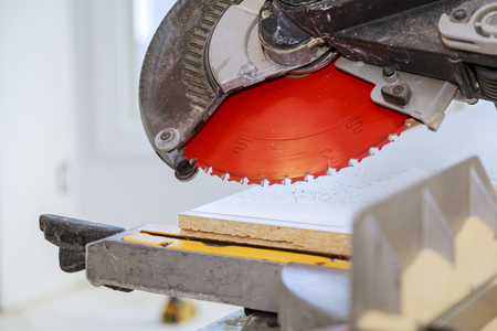Wooden plank on a circular saw Electro saw for cutting wooden shelves Stock Photo