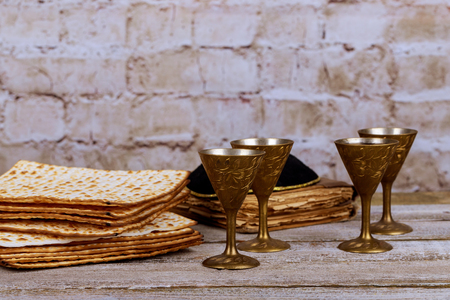 Symbols of Passover background. wine and matzoh jewish holiday bread over wooden board.