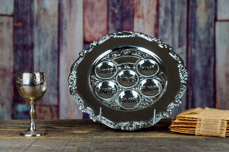 Jewish holidays Passover Pesach matzah and a silver cup full of wine with a traditional blessing Stockfoto