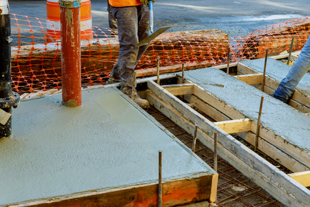 Construction worker leveling concrete pavement. Masonry construction workers smooth freshly poured concrete using bullfloat