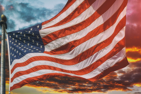 American flag flying, flag USA over beautiful Sunset sunrise with clouds, in pink and purple shades sky sunrise clouds 写真素材