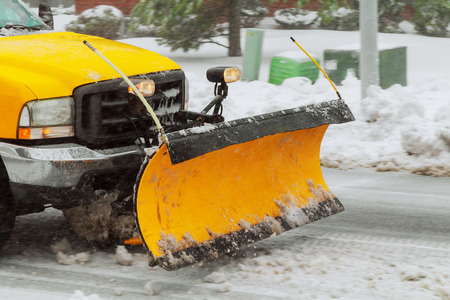 Snow plow cleaning snow from city road snow blizzard clearing roads from snow