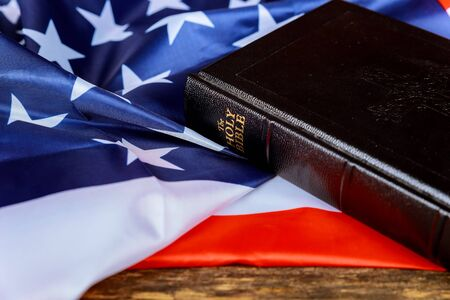 United States Flag and Holy Bible on Distressed Wood Background