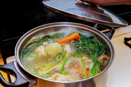 Ingredients for preparing chicken bone broth in a pot - chicken, onions, celery root, carrots, parsley Stock Photo - 97329870