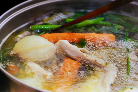 cook chicken broth Adding chicken wings into saucepan. Cooking chicken broth.