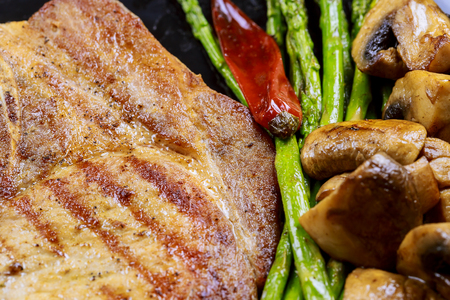 Grilled pork steaks with herbs, asparagus, mushrooms fry on stone slate background close up. Hot Meat Dishes