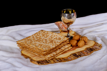 Red kosher wine with a white plate of matzah or matza and a Passover Haggadah on a vintage wood background Perfect for your Passover design mock up.