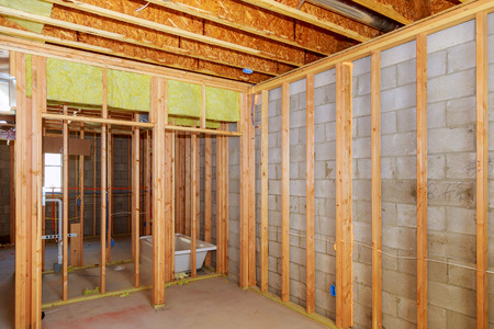 Remodeling a home bathroom, moving plumbing for new sinks Interior wall framing with piping installation in the basement Stock Photo