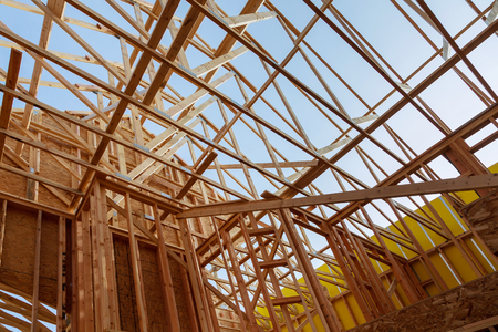 New construction home framing against blue sky, closeup of ceiling frame. Wood building frame structure on a new development site Stock Photo
