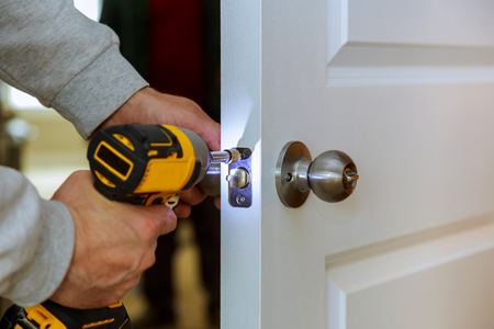 Carpenter Install Door Lock Using Screwdriver At Home installation of locks on the door Stockfoto