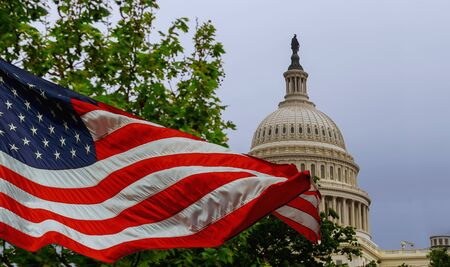 The US Capitol building with a waving American flag superimposed on the sky Capitol Hill in Washington DC Stock Photo