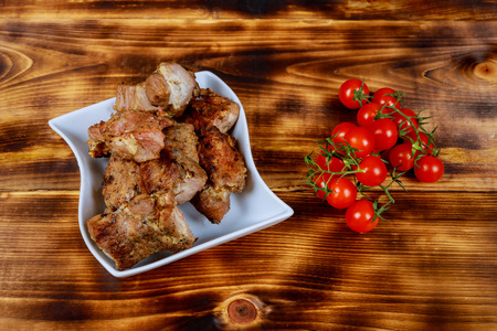 Shashlyk pork on skewers on a dark wooden board with tomatoes, onions, spinach and sauces, wooden light background with copy space Stock Photo