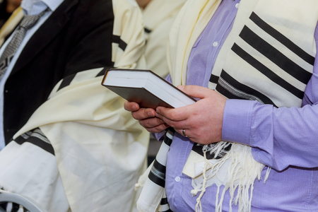 Hands holding a jewish prayer book the synagogue