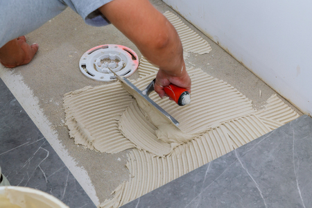 Troweling Mortar Onto A Concrete Floor In Preparation For Laying