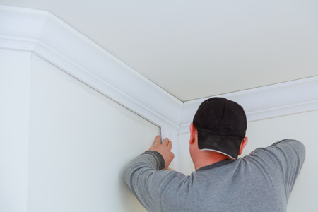 Installation of ceiling on detail of intricate corner crown molding Banque d'images - 100734300
