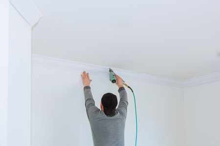 Man constructor renovates room interior with a wood crown molding in the ceiling Banque d'images - 100718281
