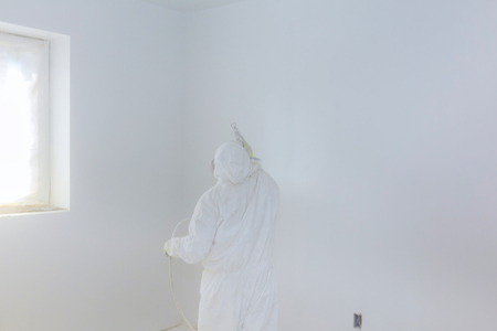 Worker painting wall with Airless Spray Gun in white color.