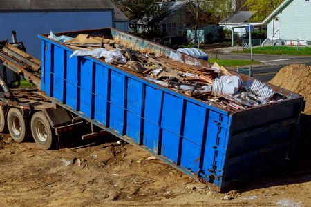 Truck loading a recycling garbage full skip waste management container Stockfoto