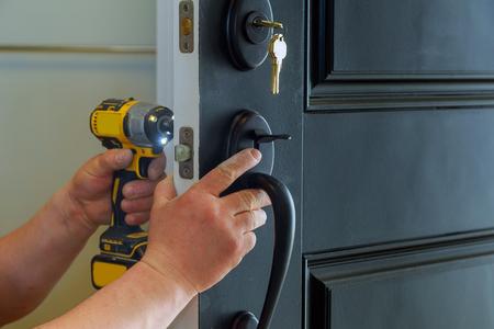 Primer plano de un cerrajero profesional instalando una nueva cerradura en la puerta exterior de una casa con el interior de las partes internas de la cerradura Foto de archivo