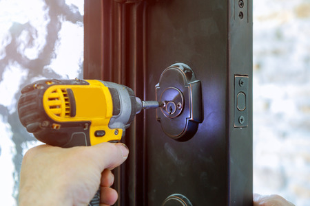 Install the door with a lock, close-up. Carpenter the screw, using an drill screwdriver, Stock Photo