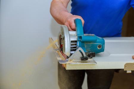 man using a circular saw for cutting wood door construction and home renovation, repair tools