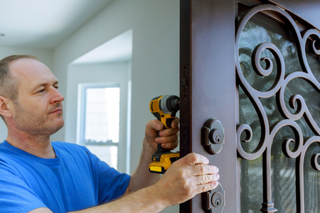The carpenter installs a reliable resistant lock in the metal door. using screwdriver