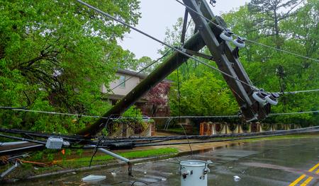 Der Sturm verursachte schwere Schäden an den Stromleitungen der Strommasten über einer Straße, nachdem die Hurricanepoles in die Schräglage gefallen waren. Standard-Bild - 101727543