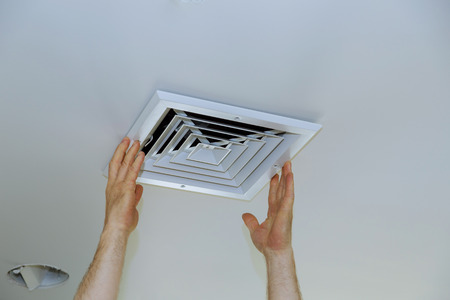 Close up man hand installing vent cover from ceiling mounted air conditioner. Standard-Bild