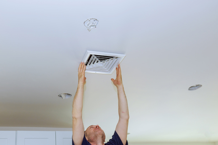 Installing New white air conditioning vent closeup Ceiling Mounted Air Conditioner.
