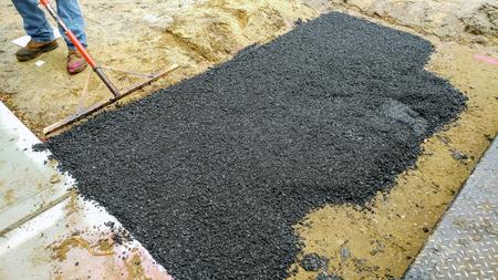 Applying new hot asphalt using road construction Workers on Asphalting paver street repairing works
