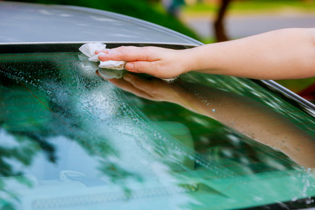 women hand dry wiping car surface with microfiber cloth after washing at parking lot