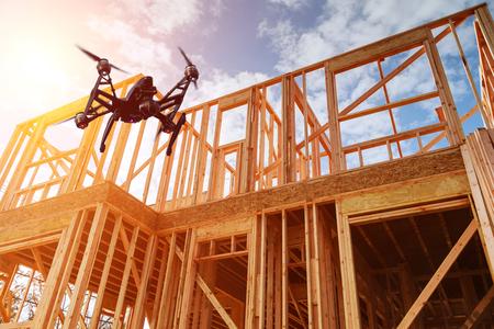 Quadcopter drone noir avec caméra survolant la maison de construction résidentielle cadrage contre un ciel bleu. Construction de toiture. Construction en bois
