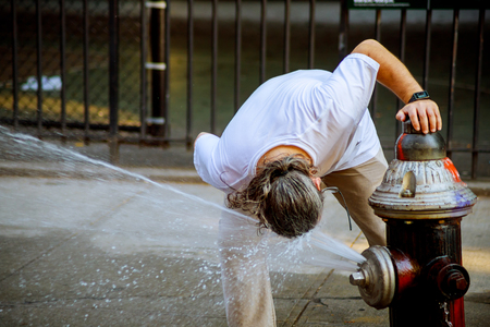 The man have fun running a strong heat temperature the water in the Fire hydrant Stock Photo