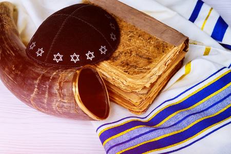 Top view of shofar horn on white prayer talit. Prayer Shawl - Shofar torah and a kippah a yamolka horn jewish religious symbol.